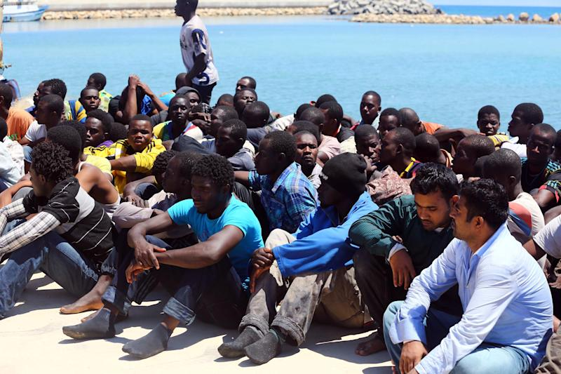 Illegal migrants sit after they were rescued by the Libyan coastguard when their boat started to sink of the coastal town of Garabulli, on July 17, 2014 (AFP Photo/Mahmud Turkia)