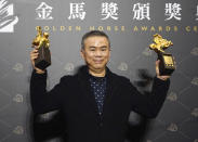 "Taiwanese director Chen Yu-hsun holds his awards for Best Director and Best Original Screenplay at the 57th Golden Horse Awards in Taipei, Taiwan, Saturday, Nov. 21, 2020. Chen won for the film ""My Missing Valentine"" at this year's Golden Horse Awards - one of the Chinese-language film industry's biggest annual events. (AP Photo/Billy Dai)"