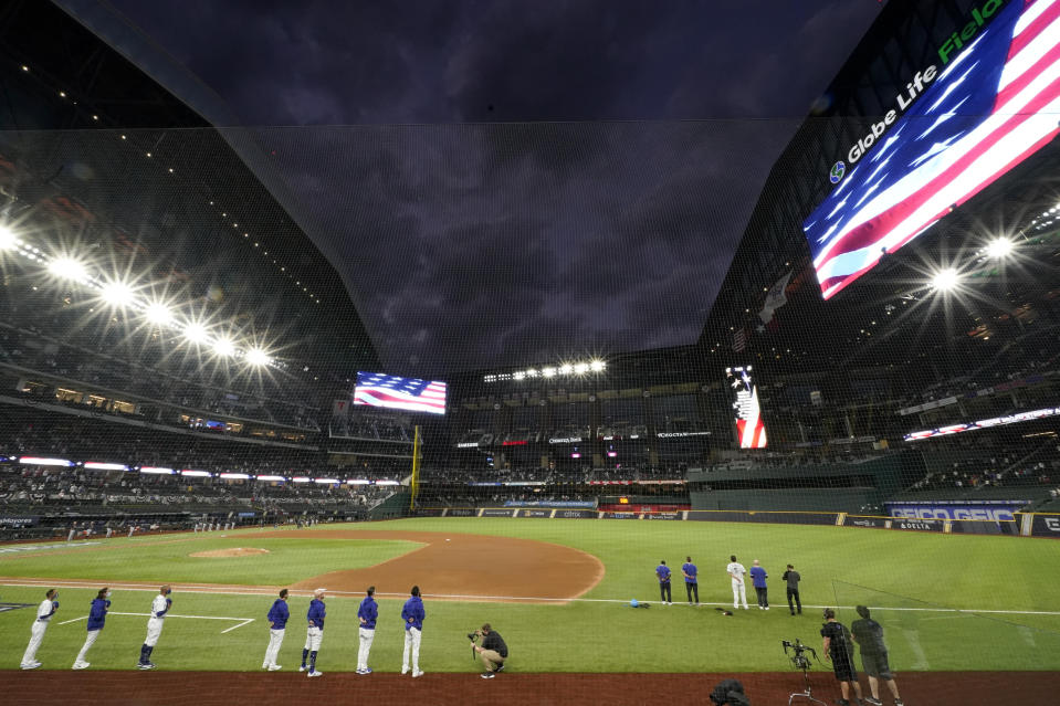 Members of the Los Angeles Dodgers stand during the national anthem before Game 7 of a baseball National League Championship Series Sunday, Oct. 18, 2020, in Arlington, Texas. Most of the seats of a new $1.2 billion, 40,518-capacity will be empty among the smallest crowd to view a World Series game in more than a century. (AP Photo/Eric Gay)
