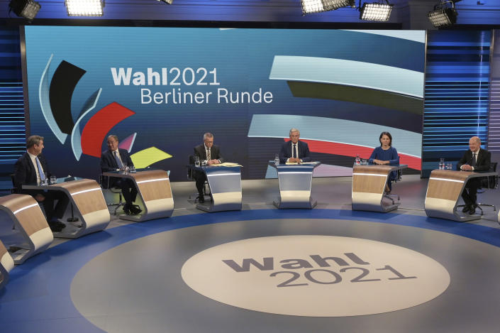 """From left: CSU leader Markus Soeder, Armin Laschet of the CDU, the CDU/CSU's candidate for chancellor, moderators Rainald Becker and Peter Frey, Annalena Baerbock, candidate for chancellor of the Green Party, Olaf Scholz, candidate for chancellor of the SPD, prepare to talk about the Bundestag election in an election studio of ZDF at the """"Berliner Runde"""" Sunday Sept. 2021 in Berlin. Projections show Germany's center-left Social Democrats locked in a very close race with outgoing German Chancellor Angela Merkel's center-right bloc, which is heading toward its worst-ever result in the country's parliamentary election. (Sebastian Gollnow/Pool via AP)"""