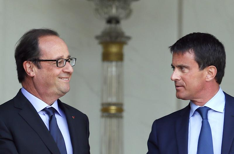 French President Francois Hollande (L) and French Prime Minister Manuel Valls leave the Elysee presidential palace in Paris after a weekly cabinet meeting on August 20, 2014