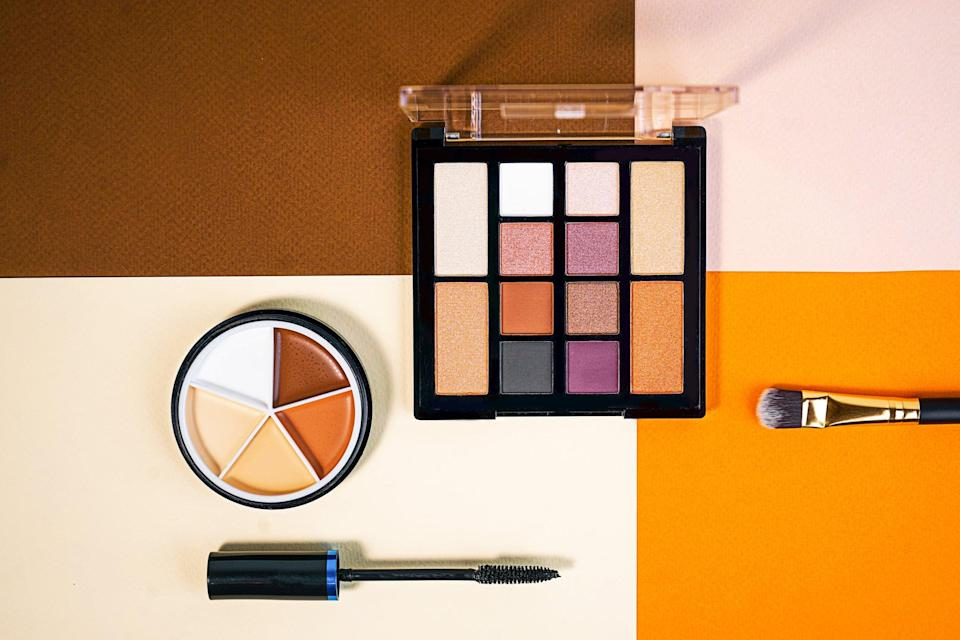 Set of beauty products laid out on a colorful background. Decorative cosmetics and makeup brushes on a pink, brown, beige and orange background, top view. Copy space.