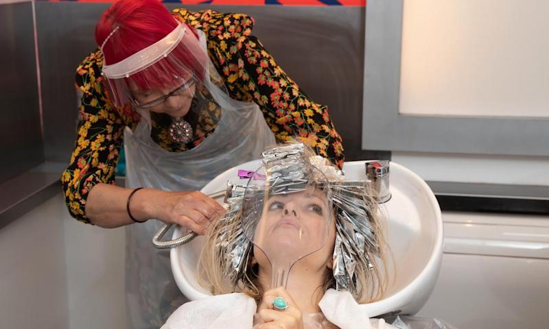A client has her hair washed behind a protective shield at Tusk Hair stylists in Camden, north London.