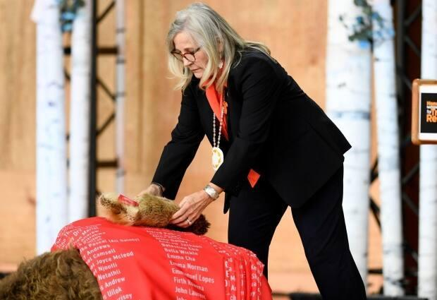 Marie Wilson, former commissioner of the Truth and Reconciliation Commission, is seen in 2019 placing a bundle of beaver skin on the ceremonial cloth with the names of children who died in residential schools.