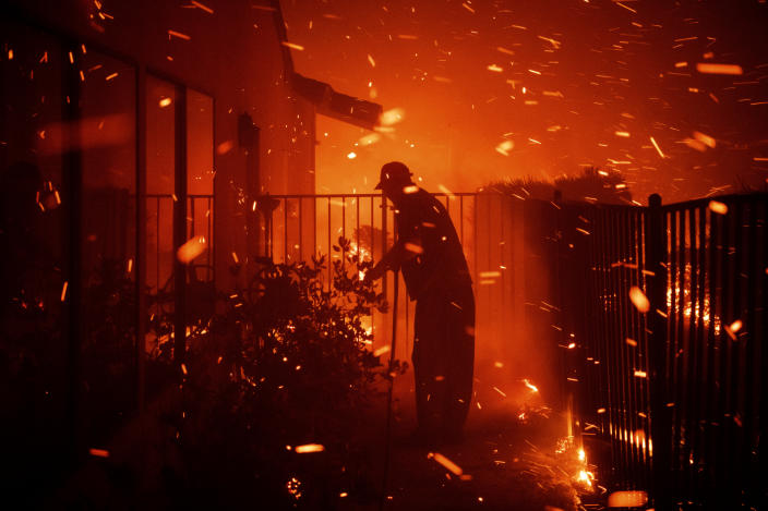 Jerry Rowe uses a garden hose to save his home on Beaufait Avenue from the Saddleridge fire in Granada Hills, Calif., Friday, Oct. 11, 2019.  (Photo: Michael Owen Baker/AP)