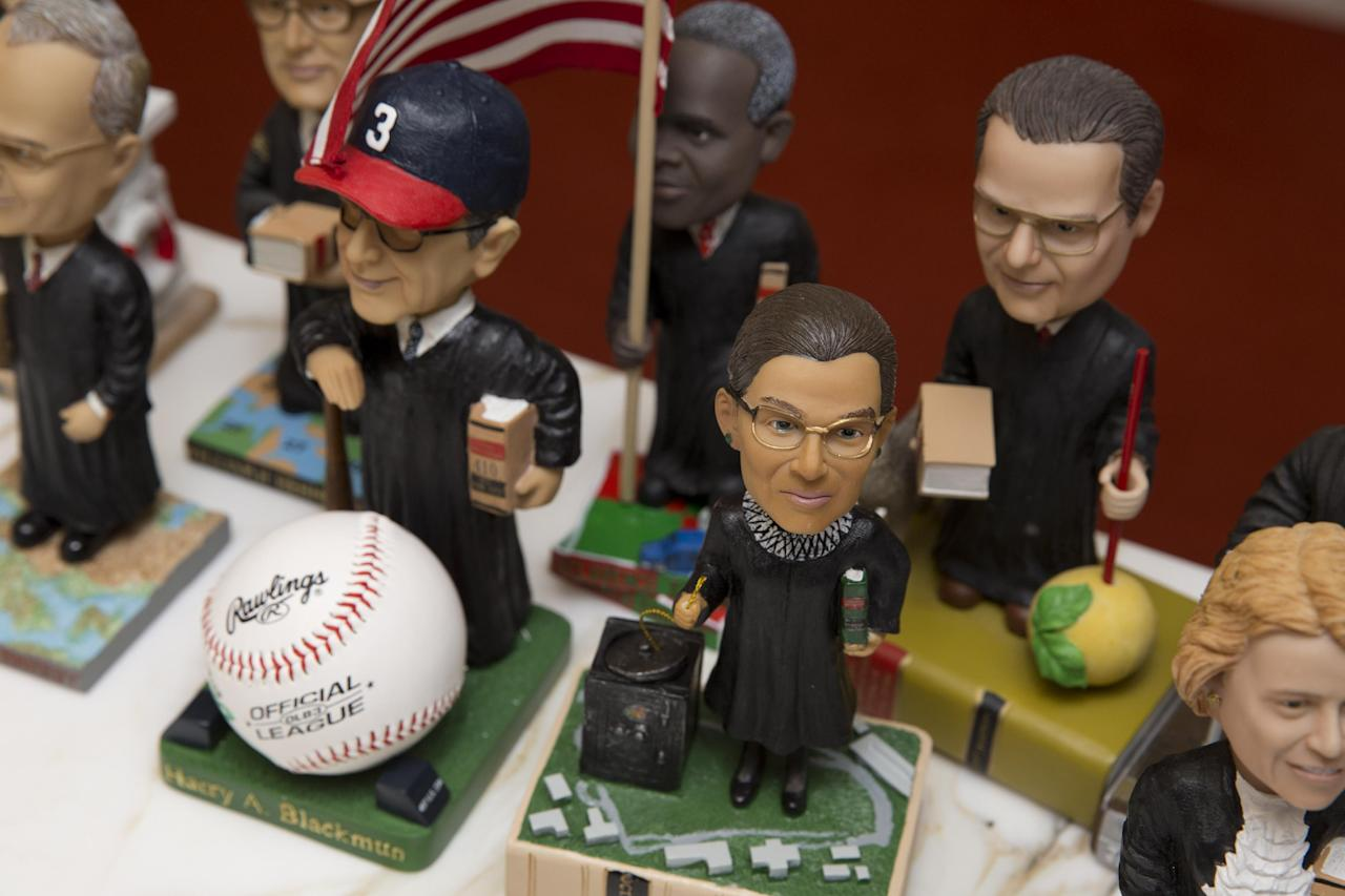 This photo taken Nov. 20, 2103 shows bobblehead dolls representing Supreme Court Justices, including Ruth Ginsburg, center, in Washington. They are some of the rarest bobblehead dolls ever produced. They're released erratically. They're given away for free, not sold. And if you get a certificate to claim one, you have to redeem it at a Washington, DC, law office. The limited edition bobbleheads of U.S. Supreme Court justices are the work of law professor Ross Davies, who has been creating them for the past ten years. When finished, they arrive unannounced on the real justices' desks, secreted there by unnamed confederates. And fans will go to some lengths to get one. (AP Photo/Jacquelyn Martin)