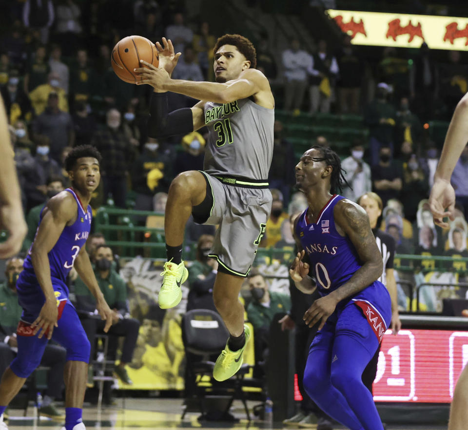 File-Baylor guard MaCio Teague, front left, scores past Kansas guard Marcus Garrett in the second half of an NCAA college basketball game, Monday, Jan. 18, 2021, in Waco, Texas. Teague and Davion Mitchell, two of the league's best shooters, were part of a Big 12-record 23-game winning streak last season in their debuts as Baylor starters. Those former transfers had also gone through a redshirt season together. (Rod Aydelotte/Waco Tribune-Herald via AP, File)