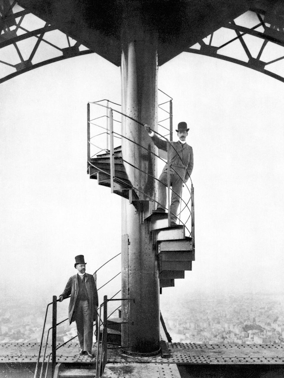 Gustave Eiffel (left) and a friend explore the newly built Eiffel Tower in Paris in 1889, the year of the Centennial Exposition for which it was built.