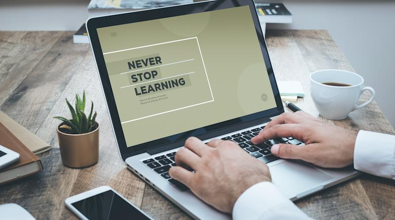 """A person typing on a notebook computer that says """"Never stop learning"""" on the screen."""