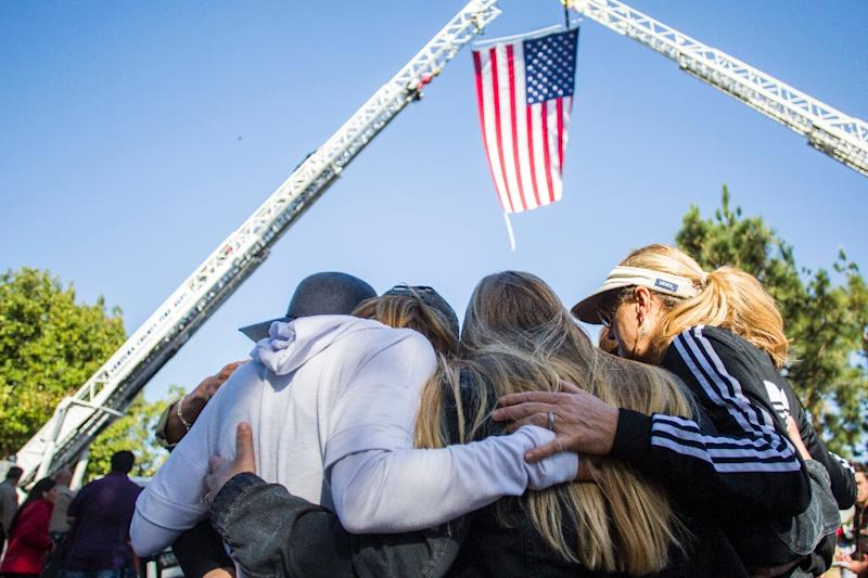 Friends hug outside Los Robles Medical Center in Thousands Oaks, California, paying tribute to a police officer killed at the Borderline Bar and Grill (AFP Photo/Apu Gomes)