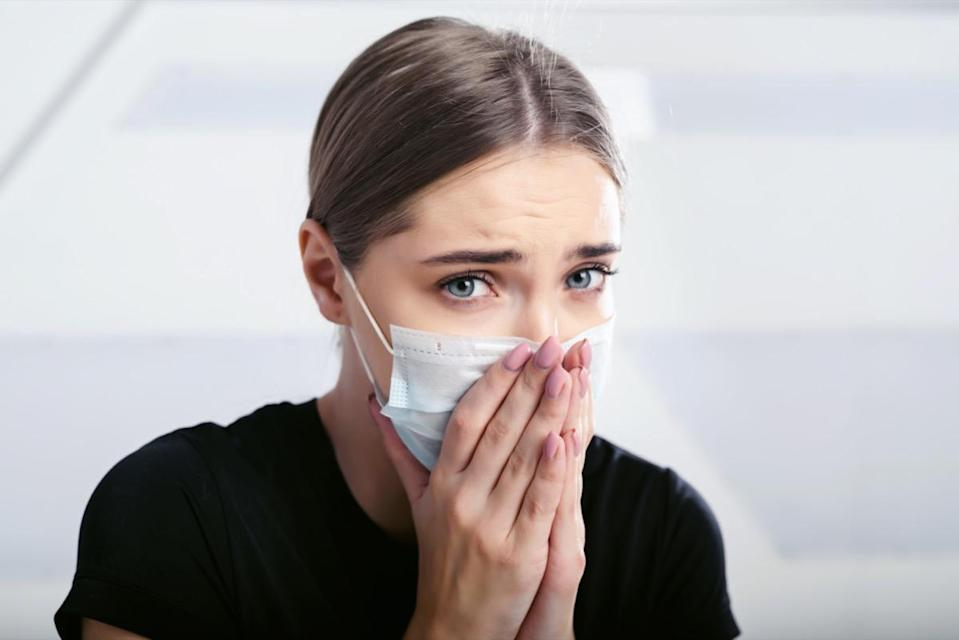 sick with a new coronavirus coughs in a disposable facial mask