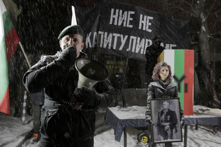A far-right Bulgarian nationalist speaks on a megaphone during a gathering, in the country's capital, to honour a World War II general known for his anti-Semitic and pro-Nazi activities, in Sofia, Saturday, Feb. 13, 2021. Braving sub-zero temperatures, hundreds of dark-clad supporters of the Bulgarian National Union group flocked to a central square where they had planned to kick off the annual Lukov March, a torch-lit procession held every February to the former house of Gen. Hristo Lukov. (AP Photo/Valentina Petrova)