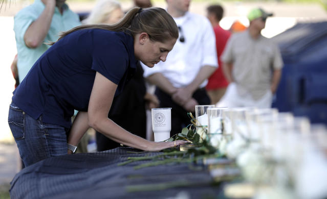 <p>A woman pauses at a table with 10 candles, roses and bibles displayed during a prayer vigil following a deadly shooting at Santa Fe High School in Santa Fe, Texas, on Friday, May 18, 2018. (Photo: David J. Phillip/AP) </p>