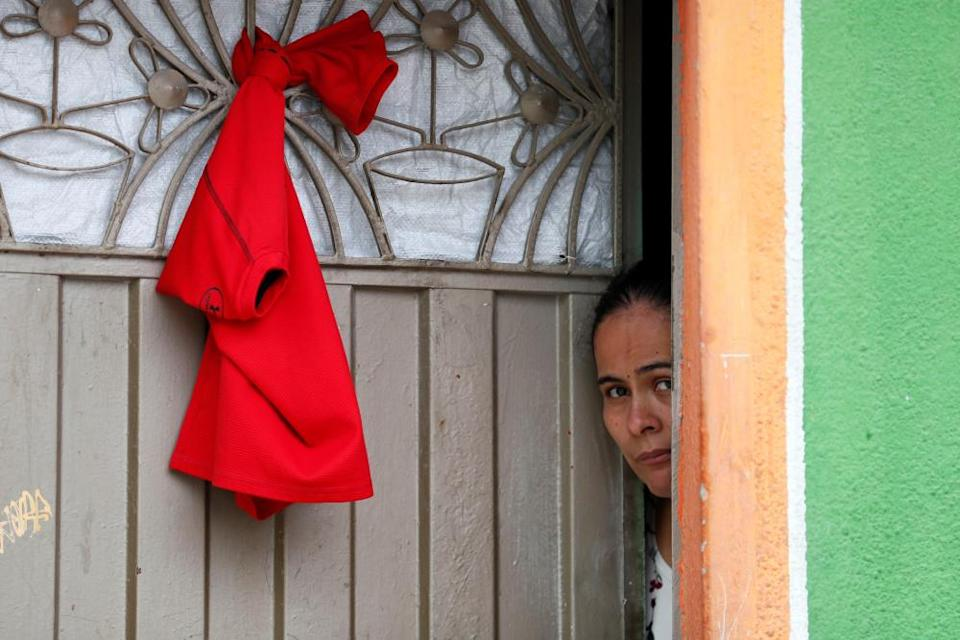 Residents of Ciudad Bolivar place red flags on the facades of their houses, south of Bogota, Colombia, on 17 April.