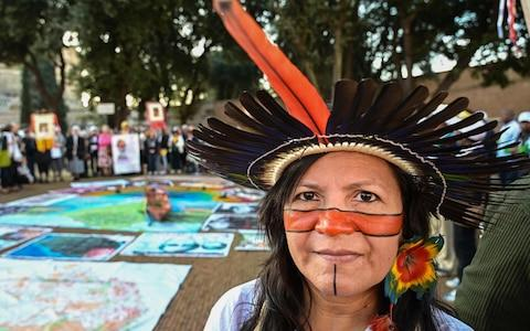 An indigenous leader participating in the Special Assembly of the Synod of Bishops for the Pan-Amazon Region takes part in a procession on October 19, 2019 between Rome's Castel Sant'Angelo and the Vatican's St. Peters Square - Credit: AFP