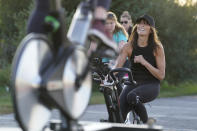 Jeanne Carter, co-owner of Fuel Training Studio, in Newburyport, Mass., right, works out on a stationary exercise bike during a spinning class in a parking lot outside the gym, Monday, Sept. 21, 2020, in Newburyport. The gym's revenue is down about 60% during the COVID-19 pandemic. Fuel Training Studio plans to continue holding outdoor classes into the winter with the help of a planned greenhouse-like structure with heaters but no walls. (AP Photo/Steven Senne)
