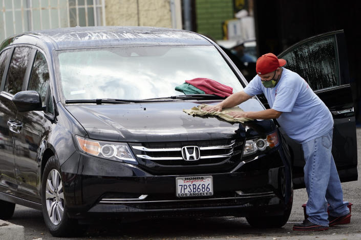 FILE - In this May 20, 2021, file photo, a worker wears a mask as he dries a car amid the COVID-19 pandemic at hand car wash shop, in Los Angeles. California workplace regulators are considering Thursday, June 3, 2021, whether to end mask rules if every employee in a room has been fully vaccinated against the coronavirus, frustrating business groups by eying a higher standard than the state plans to soon adopt for social settings. (AP Photo/Marcio Jose Sanchez, File)