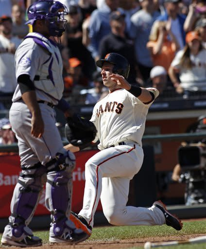 San Francisco Giants' Buster Posey, right, slides into home behind Colorado Rockies catcher Wilin Rosario during the sixth inning of a baseball game, Sunday, May 26, 2013 in San Francisco. (AP Photo/George Nikitin)