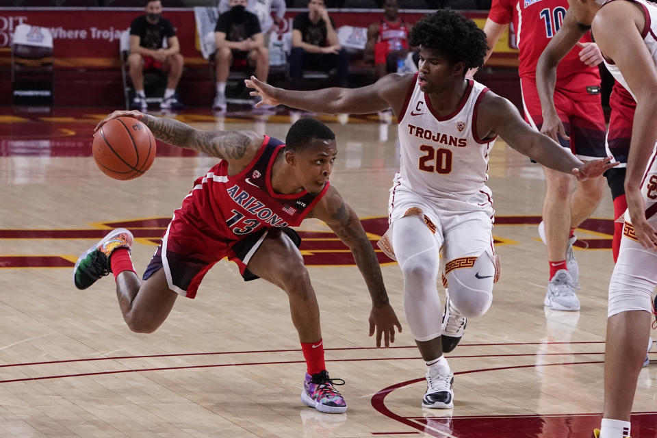 Arizona guard James Akinjo (13) is defended by Southern California guard Ethan Anderson (20) during the first half of an NCAA college basketball game Saturday, Feb. 20, 2021, in Los Angeles. (AP Photo/Marcio Jose Sanchez)
