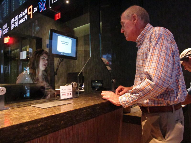 This Sept. 4, 2019 photo shows a customer checking the odds at the sports book at the Borgata casino in Atlantic City, N.J. Figures released Thursday, Sept. 12, 2019 show more than $293 million was wagered on sports in New Jersey in August, helping Atlantic City's nine casinos increase their revenue by 13% compared to a year ago. (AP Photo/Wayne Parry)