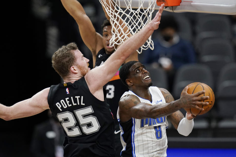 Orlando Magic forward Dwayne Bacon (8) drives to the basket past San Antonio Spurs center Jakob Poeltl (25) during the second half of an NBA basketball game in San Antonio, Friday, March 12, 2021. (AP Photo/Eric Gay)