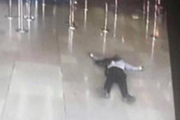 Shot: The man lies on the terminal floor (AP)