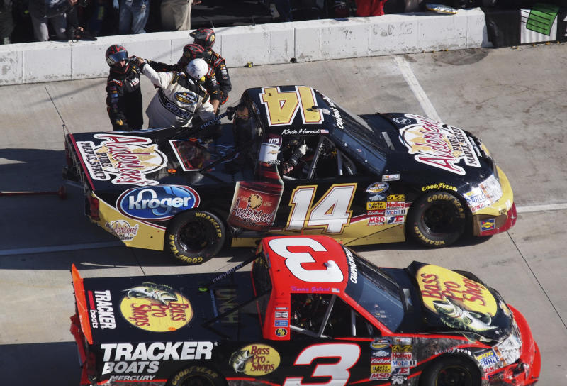 A NASCAR official breaks up a scuffle after driver Kevin Harvick (14) stopped in the pit of Ty Dillon (3) during the NASCAR Camping World Truck Series truck race at Martinsville Speedway in Martinsville, VA., Saturday, Oct. 26, 2013. (AP Photo/Steve Sheppard)