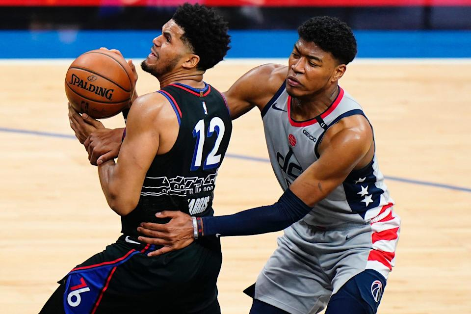 Philadelphia 76ers' Tobias Harris, left, is grabbed by Washington Wizards' Rui Hachimura during the first half of Game 1.