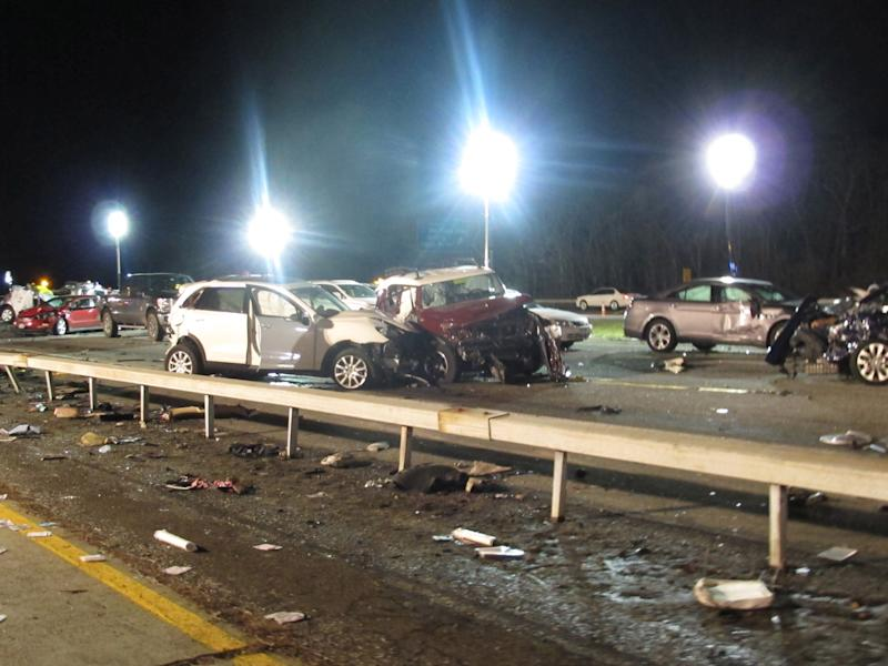 Damaged vehicles and debris are strewn across the Long Island Expressway following a chain reaction crash on Wednesday, Dec. 19, 2012, in Shirley, N.Y. At least one person was killed and 32 injured. (AP Photo/Frank Eltman)