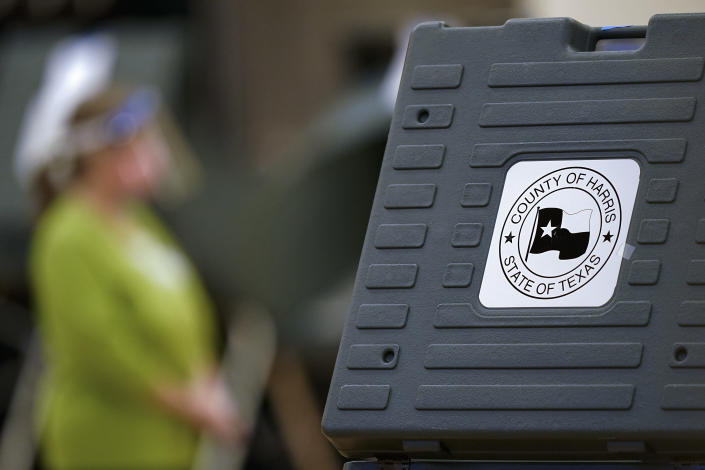 FILE - In this Nov. 3, 2020, file photo an election poll worker stands among voting machines in Houston. A group of researchers reports a series of minor errors in Texas' election results across the states. The discrepancies concern only a few hundred votes and would not have made a difference in races. But they show how new partisan demands for election audits overlook actual weaknesses in election systems. Dozens of Texas' Republican lawmakers have called for an audit of the state's largest counties' election results. (AP Photo/David J. Phillip, File)