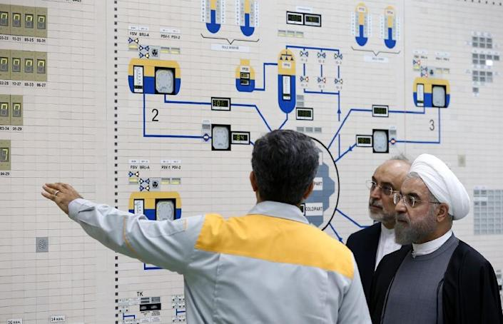 AIranian President Hassan Rouhani (R) and Iran's Atomic Energy Organisation chief Ali Akbar Salehi (2nd from R) listen to a technician in the control room of the Bushehr nuclear power plant in on January 13, 2015 (AFP Photo/Mohammad Berno)