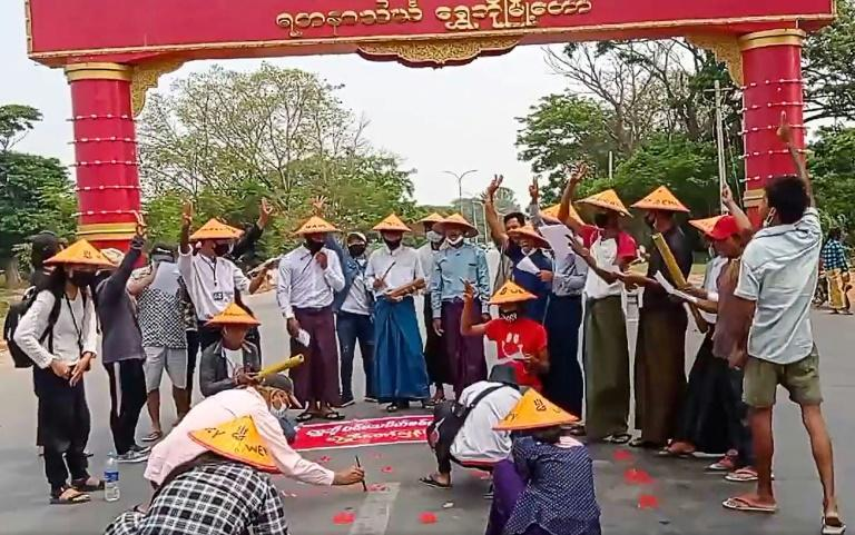 Protesters make the three-finger salute during a poetry reading in the city of Shwebo