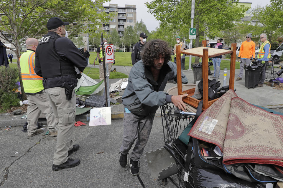 FILE - In this May 4, 2020 file photo a Seattle Police officer and other workers look on as a man wheels away a cart of his belongings from a homeless encampment being cleared, at Ballard Commons Park in Seattle. An affluent Seattle-area community has approved an ordinance prohibiting camping on public property. The city of Mercer Island says the measure will connect homeless people to shelters, but it might prove hard to enforce because of a federal court ruling. (AP Photo/Ted S. Warren,File)