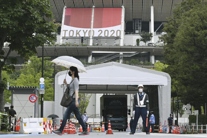 People wearing face masks walk past the National Stadium in Tokyo, Thursday, July 8, 2021. Japan is set to place Tokyo under a state of emergency that would last through the Olympics, fearing an ongoing COVID-19 surge will multiply during the Games. (Kyodo News via AP)