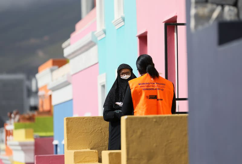 A health worker talks to residents as they conduct screening during the 21-day nationwide lockdown aimed at limiting the spread of coronavirus disease (COVID-19) in Bo Kaap, Cape Town