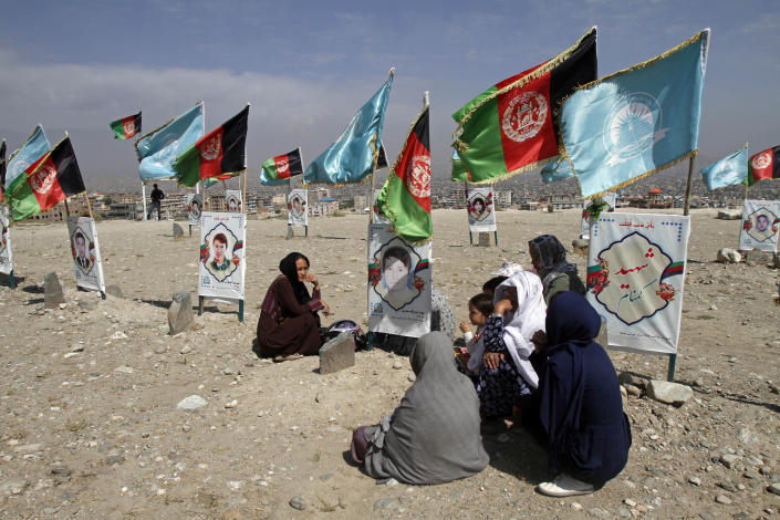Families of victims of war gather at the graves of their relatives on the outskirts of Kabul, Afghanistan, Monday, Sept 14, 2020. The families are demanding a permanent countrywide ceasefire from the parties to the intra-Afghan peace conference taking place in Doha, Qatar. (AP Photo/Rahmat Gul)