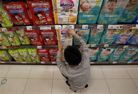 An Aeon Co Ltd's supermarket staff adjusts a slip of paper informing the two-package-per-family limit on Kao Corp's 'Merries' brand diapers on a display shelf at its Chiba outlet, east of Tokyo, March 31, 2014. REUTERS/Yuya Shino
