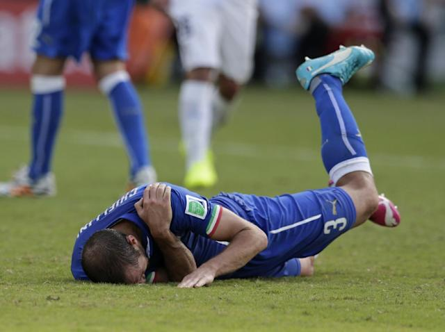 Italy's Giorgio Chiellini holds his shoulder after Uruguay's Luis Suarez ran into Chiellini's shoulder during the group D World Cup soccer match between Italy and Uruguay at the Arena das Dunas in Natal, Brazil, Tuesday, June 24, 2014. (AP Photo/Petr David Josek)