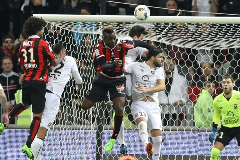 Nice's forward Mario Balotelli (C) heads the ball  during the French L1 football match Nice vs Caen on February 10, 2017 at the Allianz Riviera stadium in Nice, southeastern France