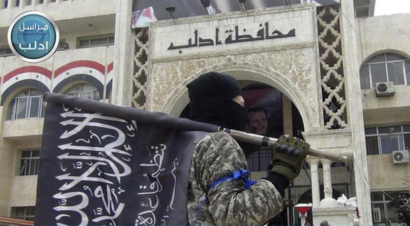 FILE - In this file photo posted on the Twitter page of Syria's al-Qaida-linked Nusra Front on March 28, 2015, a fighter from Syria's al-Qaida-linked Nusra Front holds his group flag as he stands in front of the governor building in Idlib province, north Syria. Turkey and Russia appear to have succeeded in creating a demilitarized zone along the frontlines of Syria's flashpoint Idlib region, after rebels and an al-Qaida-linked alliance pulled back their heavy weaponry in accordance with the agreement. (Al-Nusra Front Twitter page via AP, File)