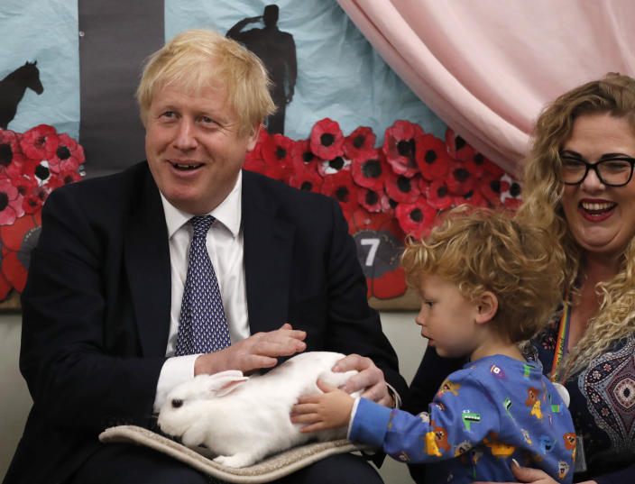 FILE - In this Thursday, Nov. 14, 2019 file photo Britain's Prime Minister Boris Johnson hold Rosie the rabbit during a visit of the West Monkton CEVC Primary School on a General Election campaign trail in Taunton, England. (AP Photo/Frank Augstein, Pool, File)