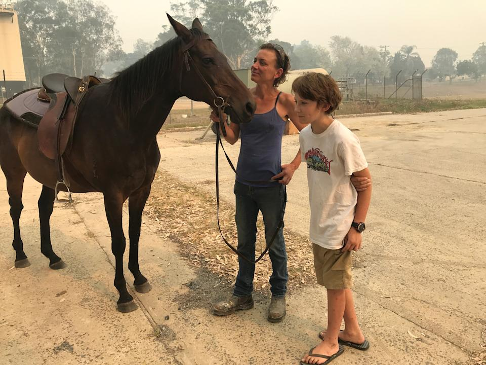 Bec Winter stands next to her son, Riley, and her horse Charmer, who she rode to safety through bushfires on New Year's Eve, in Moruya, Australia January 4, 2020. REUTERS/Jill Gralow