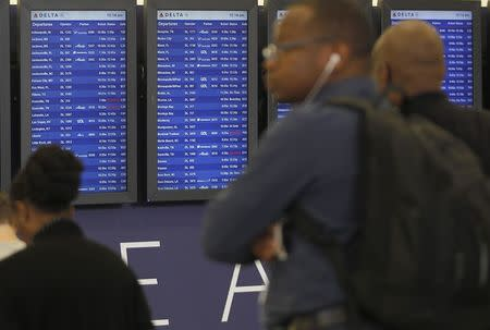 Departure boards show some Delta flights as cancelled flights after Delta Air Lines' computer systems crashed on Monday, grounding flights around the globe, at Hartsfield Jackson Atlanta International Airport in Atlanta, Georgia, U.S. August 8, 2016.  REUTERS/Tami Chappell - RTSLUJF