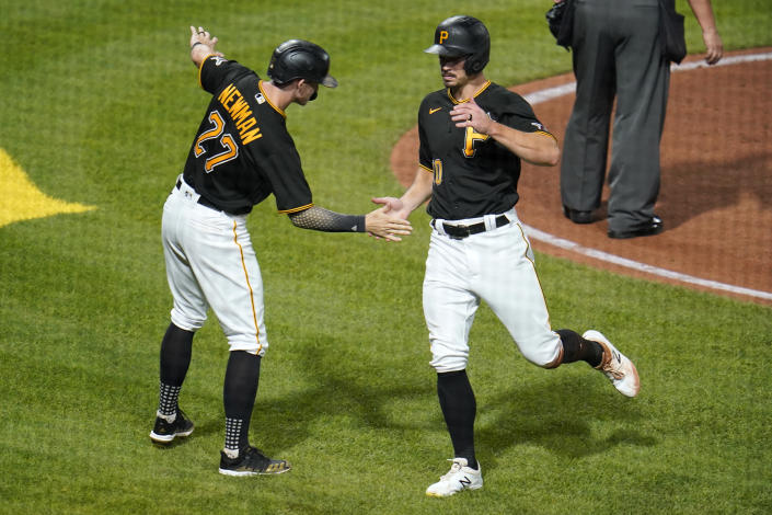 Pittsburgh Pirates' Kevin Newman (27) and Bryan Reynolds (10) celebrate after scoring on a single by Yoshi Tsutsugo and a throwing error by Cincinnati Reds centerfielder Aristides Aquino during the fifth inning of a baseball game in Pittsburgh, Tuesday, Sept. 14, 2021. (AP Photo/Gene J. Puskar)