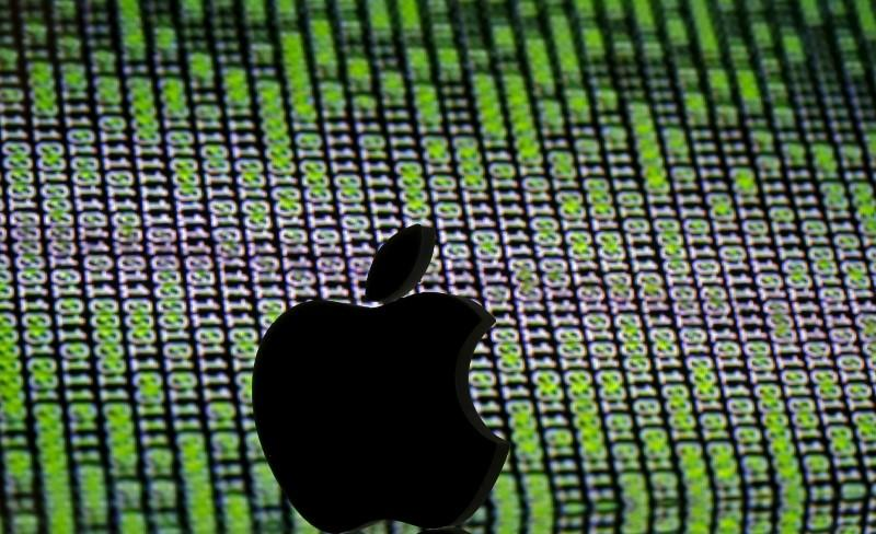 FILE PHOTO: A 3D printed Apple logo is seen in front of a displayed cyber code in this illustration