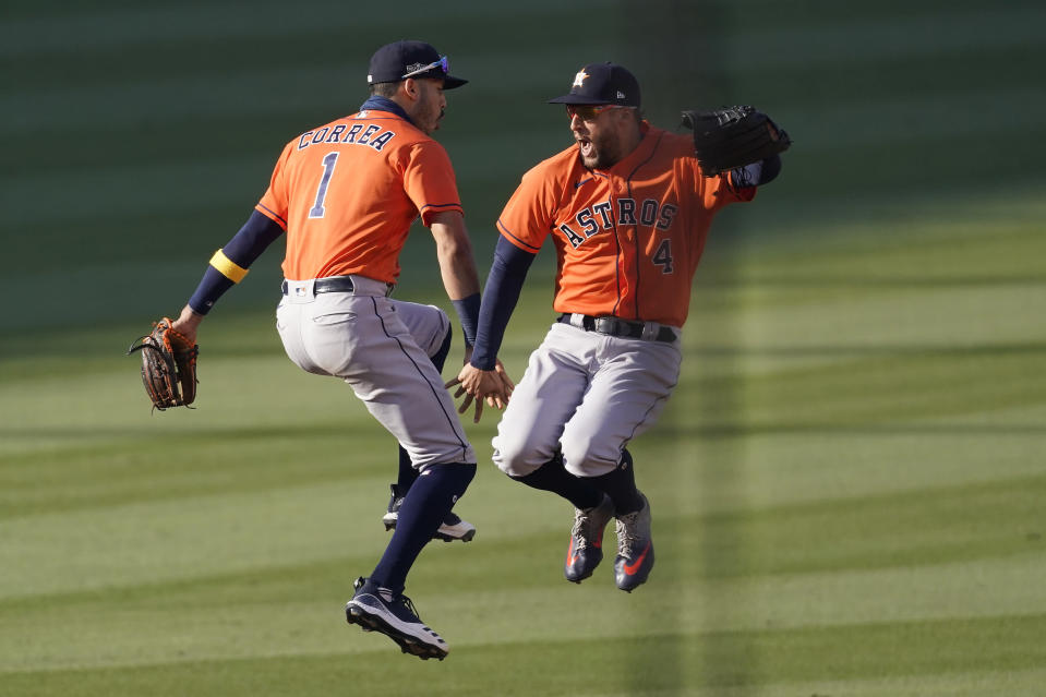 Houston Astros' Carlos Correa, left, and George Springer celebrate after the Astros defeated the Oakland Athletics in Game 2 of a baseball American League Division Series in Los Angeles, Tuesday, Oct. 6, 2020. (AP Photo/Ashley Landis)