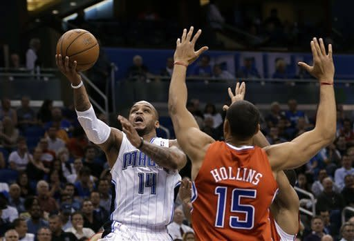Orlando Magic guard Jameer Nelson (14) gets to the basket for a shot past Los Angeles Clippers' Ryan Hollins (15) during the first half of an NBA basketball game, Wednesday, Feb. 6, 2013, in Orlando, Fla. (AP Photo/John Raoux)