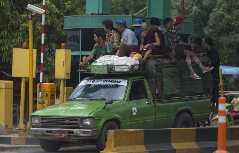 In this June 14, 2013 photo, passengers, including a Buddhist monk, travel atop a public transport passing a toll-gate in the outskirts of Yangon, Myanmar. Online car sales may also be booming. There's no official data, but over a dozen such websites are operating. There's huge room for growth in a country of over 60 million with only 38 vehicles per 1,000 people Because of the abysmal state of public transport in Yangon, a city of 5 million, those who can afford to drive, do. Those who can't cram into ancient buses perched precariously on huge tires or hitch rides on pickups outfitted with benches and makeshift roofs. (AP Photo/Gemunu Amarasinghe)