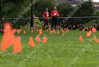 <p>People pause to look at orange flags, representing children who died while attending Indian residential schools in Canada, placed in the grass at Major's Hill Park in Ottawa, on Canada Day, Thursday, July 1, 2021. THE CANADIAN PRESS/Justin Tang</p>