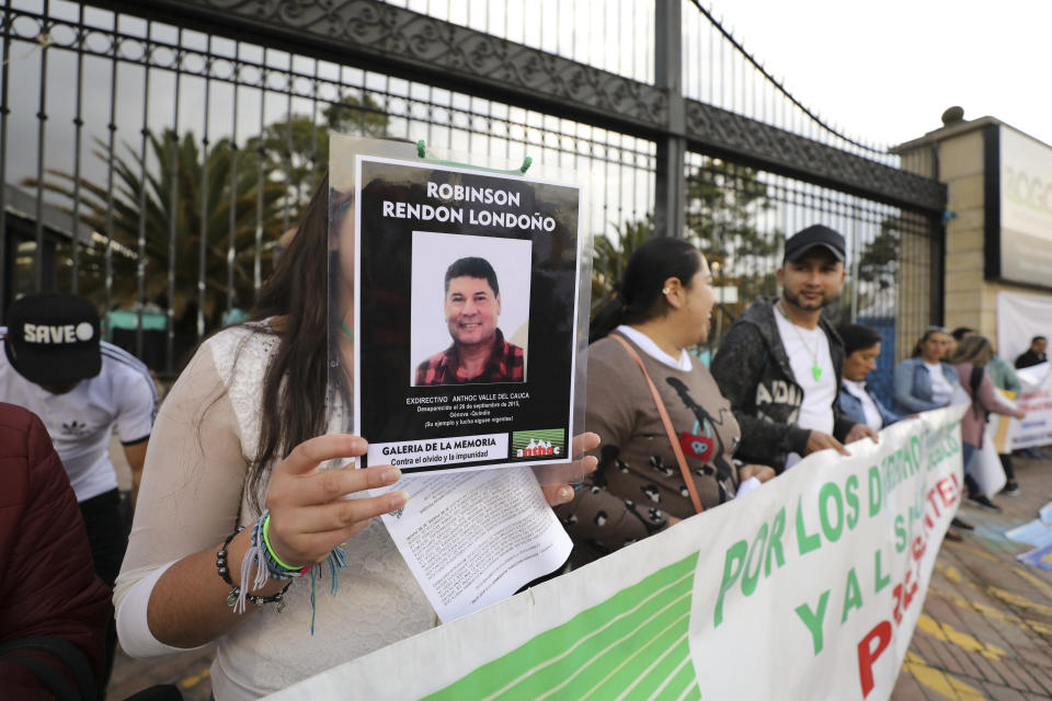 A woman holds a sign with a man's photo that say he disappeared in 2015, as she attends an anti-government protest outside the National Center for Historical Memory to call for the resignation of its director, Dario Acevedo, on Human Rights Day in Bogota, Colombia, Tuesday, Dec. 10, 2019. Protesters portray Acevedo as a henchman for the ruling conservative political party intent on masking the state's role in crimes committed during the country's long civil conflict. (AP Photo/Fernando Vergara)
